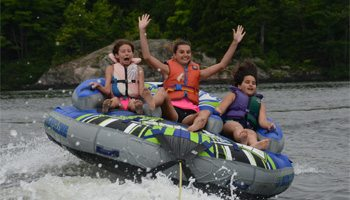 Kids having fun during summer camp on a tube in the lake.