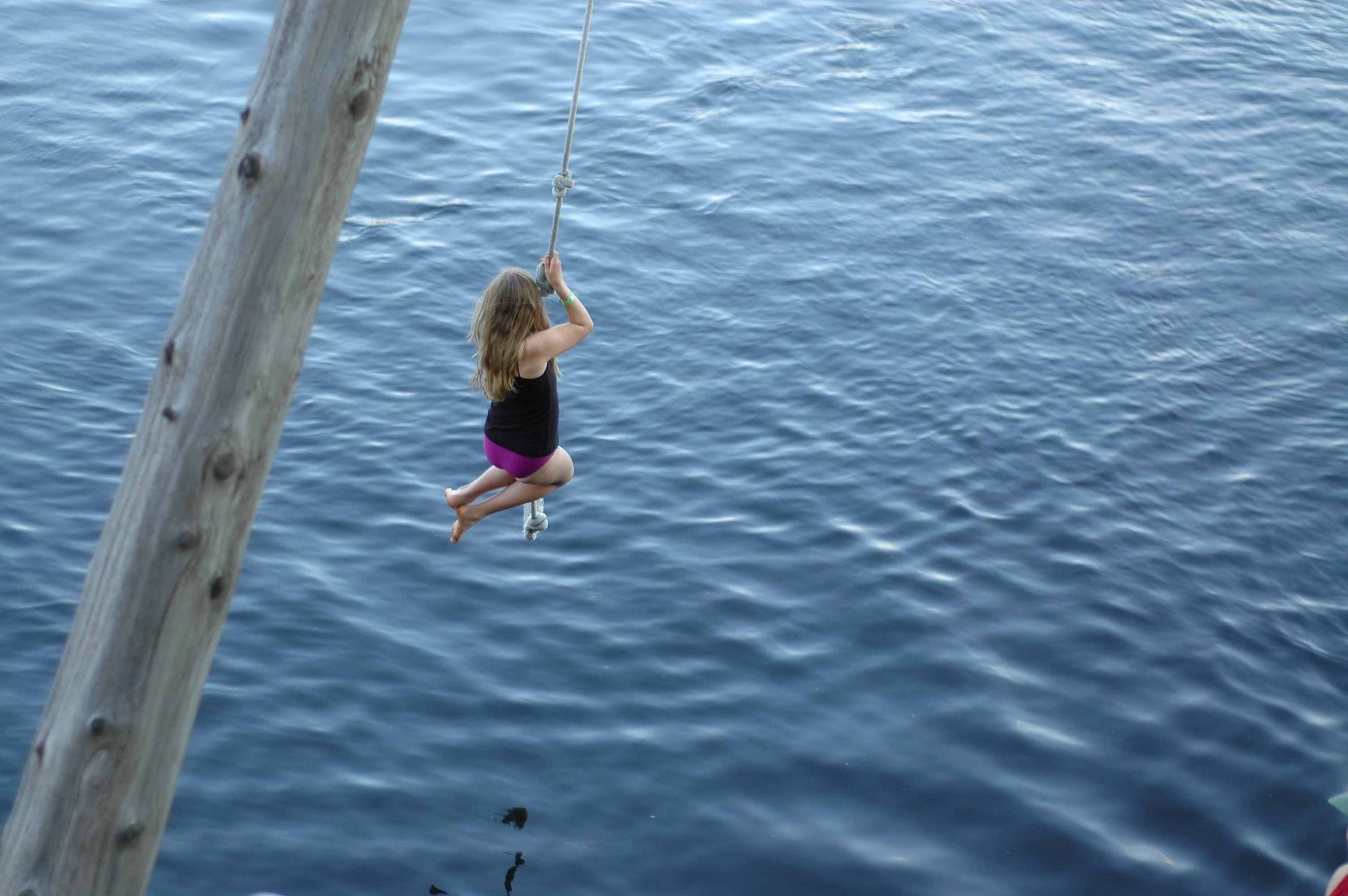 Camper rope-swinging into the water.